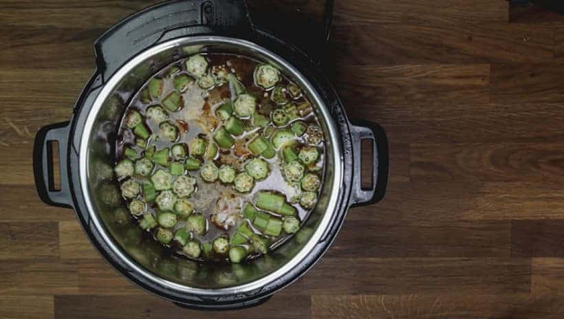 Instant Pot Gumbo Recipe (Pressure Cooker Gumbo): layer fresh chopped okra on top of chicken thighs and andouille sausage in Instant Pot Pressure Cooker