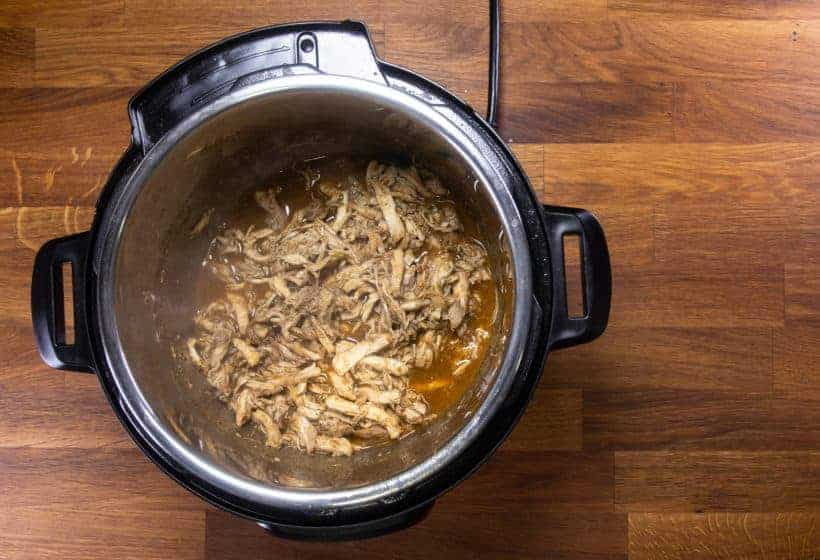 Instant Pot Chicken Tacos | Pressure Cooker Chicken Tacos: add shredded chicken in taco sauce in Instant Pot Pressure Cooker
