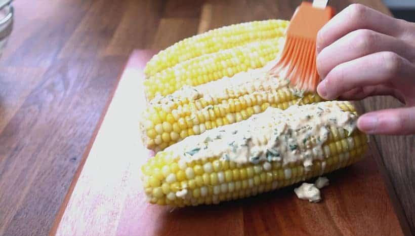 How to make Mexican Street Corn: brush cheesy mayo sauce on corn on the cob